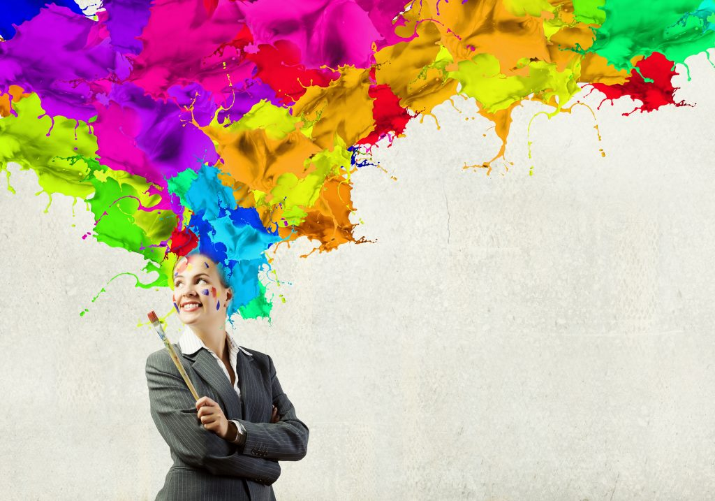 Thoughtful businesswoman with colorful splashes out of his head